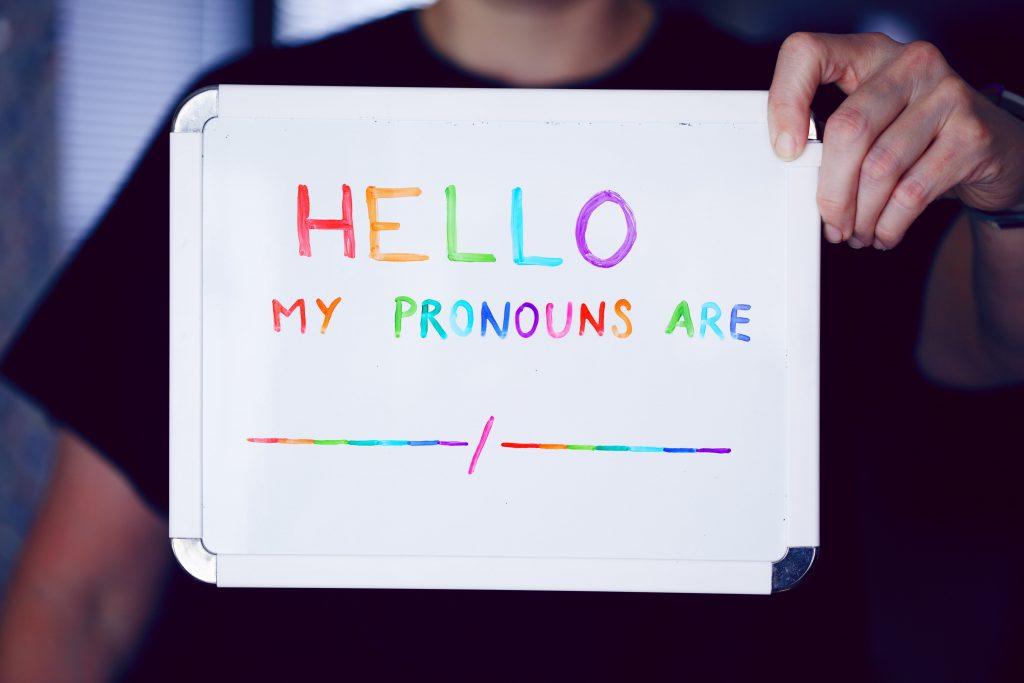 een persoon houdt een wit kartonnen bordje vast met daarop in gekleurde letters: Hello, my pronouns are: __ / __ . Dit kan nog ingevuld worden. Pronouns zijn voornaamwoorden