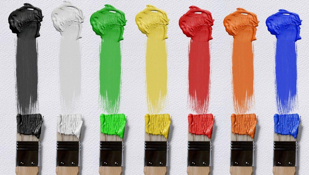 zeven kwasten op een rij die elk een eigen klodder verf van boven naar beneden hebben uitgesmeerd. Zwart, wit, groen, geel, rood, oranje, blauw