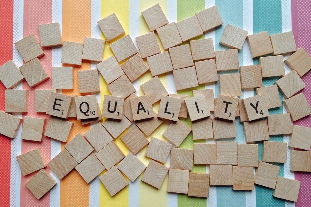 Letters: EQUALITY in scrabble steentjes, met een regenboog achtergrond
