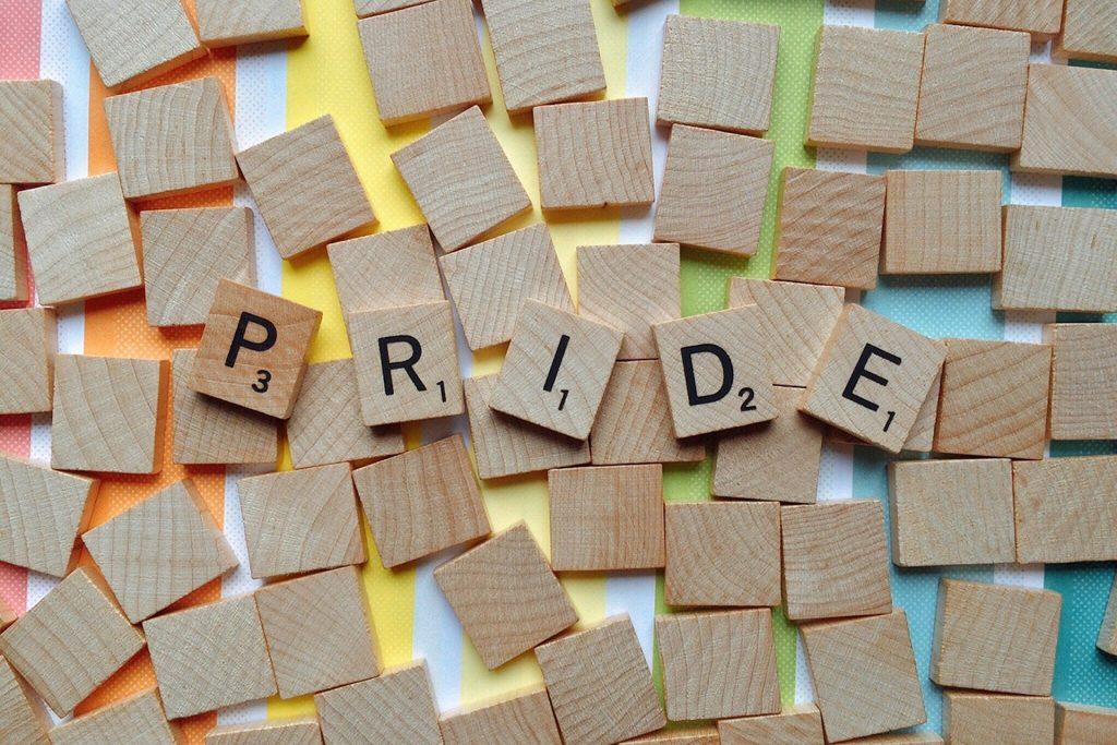 letters PRIDE op scrabble steentjes, met een regenboog achtergrond