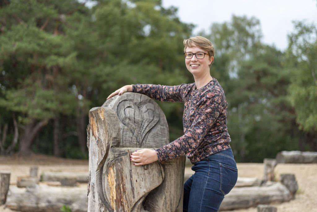 Linda klimt op een houten troon waar een hart in gegrafeerd staat. Ze heeft kort blond haar en een bril, draagt een spijkerbroek en een trui. Ze kijkt vrolijk naar de camera. Op de achtergrond boomstammen op zand en bos.